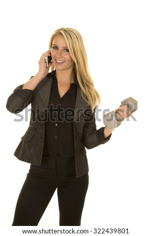 a woman with a big smile, on her cell phone, and lifting her weight. - stock photo