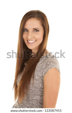 A woman with  a big smile on her face in her gray top. - stock photo