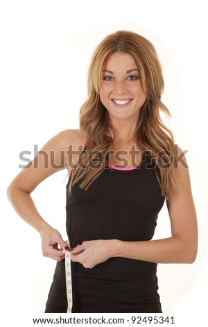 A woman with a big smile on her face measuring her waist.