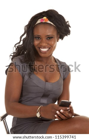 A woman with a big smile on her lips sitting on a stool with her phone in her hand. - stock photo