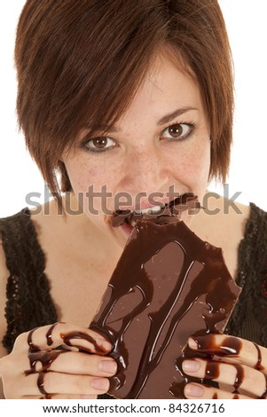 A woman with a bunch of chocolate in her mouth with chocolate covering her hands.