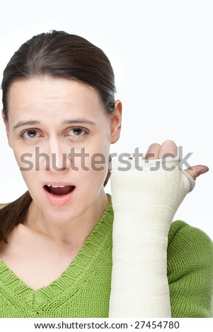 A woman with a cast on her arm on a white background - stock photo
