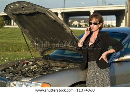 A woman with a cell phone and what appears to be car trouble. - stock photo
