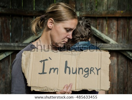 "A woman with a child holding a sheet of paper. On the paper label sheet, ""I'm hungry."""