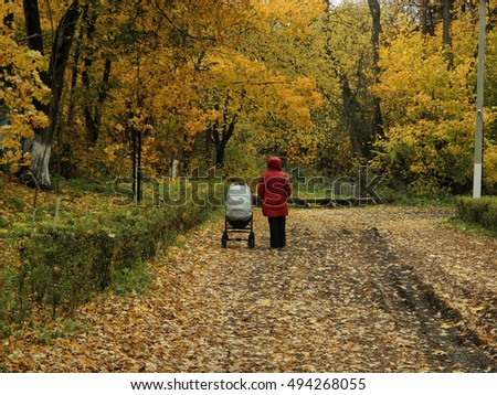 A woman with a child walks in autumn park