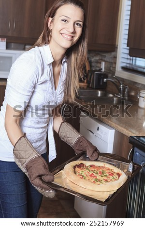 A woman with a delicious pizza on the kitchen - stock photo