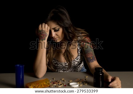 A woman with a depressed expression on her face, looking down at the drugs on the table. - stock photo