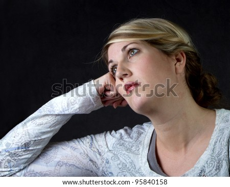 a woman with a depressed or thoughtful look on her face - stock photo