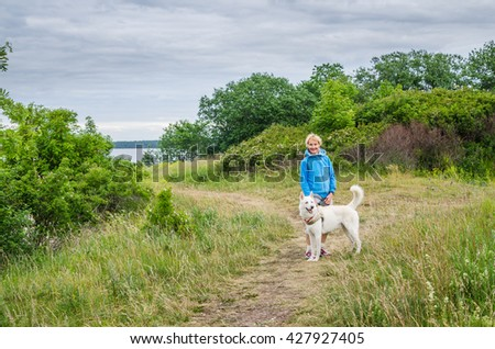A woman with a dog on the coast