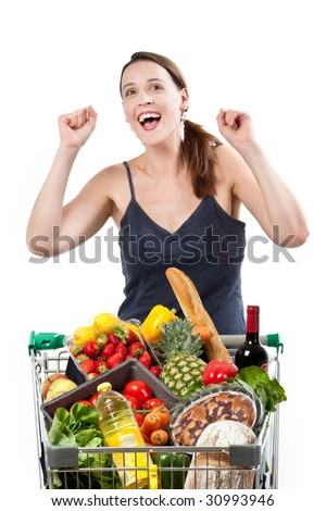 A woman with a full shopping cart happy to be shopping - punching the air on a white background