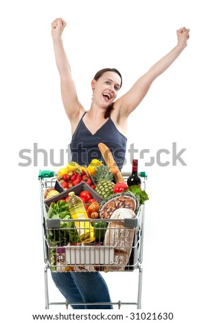 A woman with a full shopping cart happy to be shopping - punching the air on a white background - stock photo
