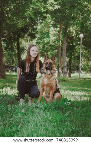 A woman with a German shepherd in a park