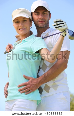 a woman with a golf club and a man putting his hands on her waist - stock photo