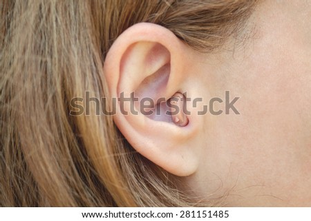 A woman with a hearing aid close-up - stock photo
