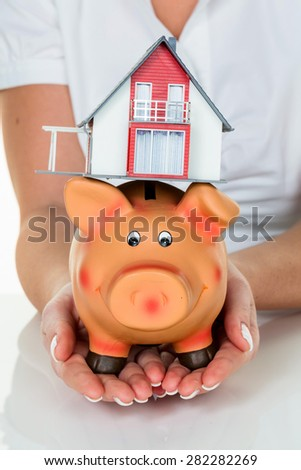 a woman with a house and a piggy bank. proper funding for the home purchase. - stock photo