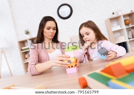 A woman with a little girl is building a lock of wooden cubes. They play together at home. It's mom and daughter.