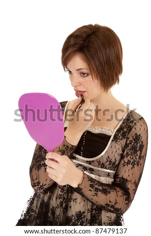 A woman with a mirror putting lipstick on looking in the mirror at herself.