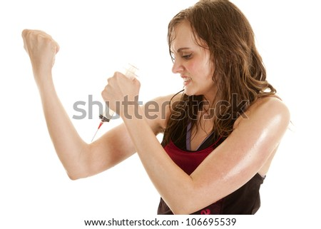 A woman with a needle pointed to her arm with an intense expression on her face - stock photo