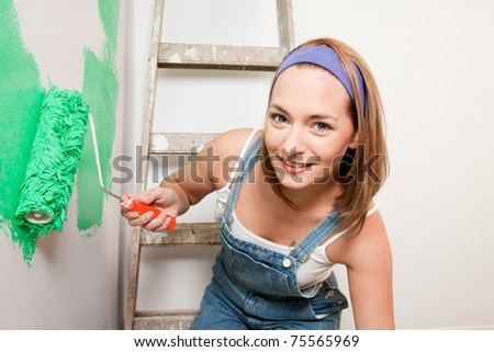 A woman with a paint roller, painting a home interior