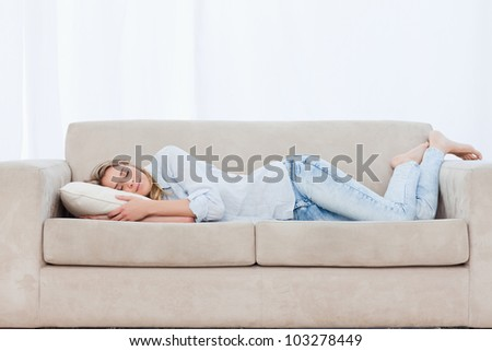 A woman with a pillow is lying on a couch sleeping - stock photo
