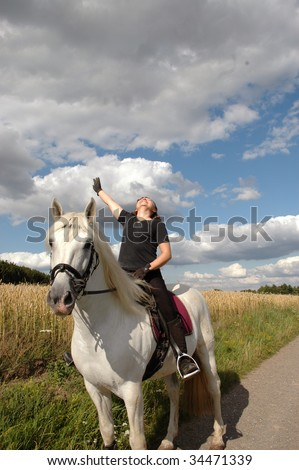 A woman with a raised hand sits on Andalusian horses.