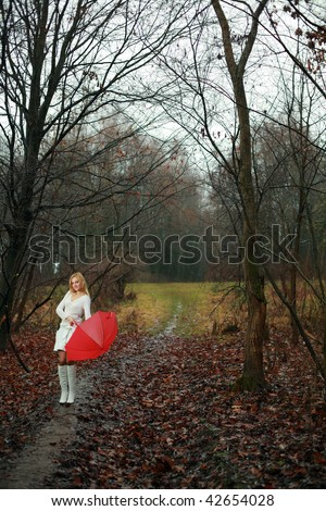 A woman with a red umbrella in autumn park