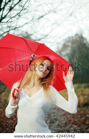 A woman with a red umbrella in the park