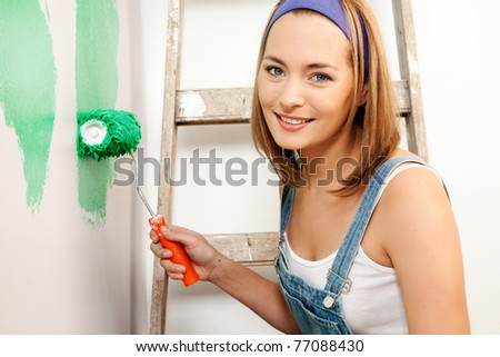 A woman with a roller brush, paiting the wall doing home improvements
