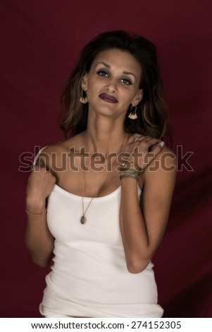 A woman with a sensual expression on her face, pulling her tank strap off her shoulder. - stock photo