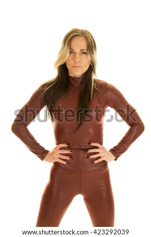 a woman with a serious expression and her hands on her hips, wearing her tight bodysuit. - stock photo