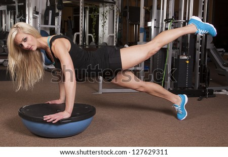 A woman with a serious expression on her face, and her hands on half ball balancing. - stock photo