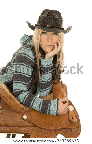 a woman with a serious expression on her face looking straight a head, leaning on her saddle. - stock photo