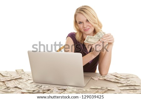 A woman with a small smile on her face holding money.