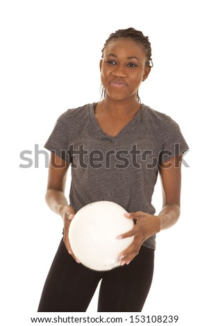 a woman with a small smile on her face holding on to her volleyball. - stock photo