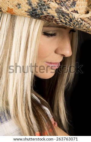 a woman with a small smile on her lips, in her western hat. - stock photo