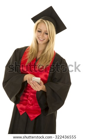 a woman with a smile graduating and looking down at her cell phone. - stock photo