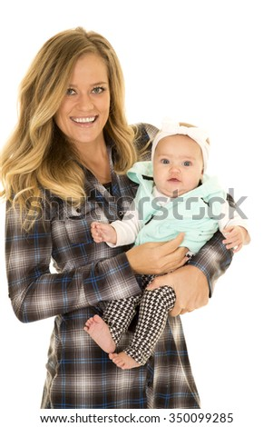 A woman with a smile holding her baby girl close to her. - stock photo