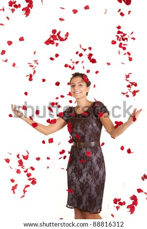 A woman with  a smile on her face being showered with rose petals.