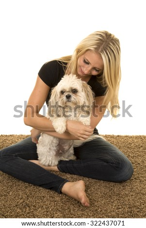 A woman with a smile on her face, holding her puppy on her lap. - stock photo