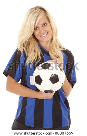 A woman with  a smile on her face holding on to a soccer ball in her soccer uniform. - stock photo
