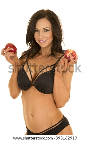 A woman with a smile on her face, holding on to her apples in her bikini