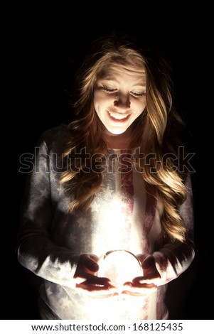a woman with a smile on her face looking down at her crystal ball. - stock photo