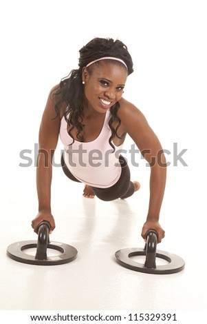 A woman with a smile on her face using push up bars. - stock photo