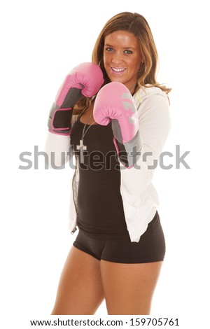 A woman with a smile on her face with her boxing gloves by her face.