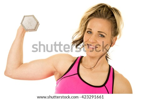 a woman with a smile on her face, working out her arms doing a curl. - stock photo