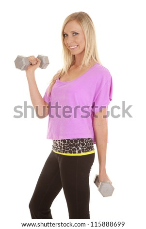 A woman with a smile on her face working out with hand weights