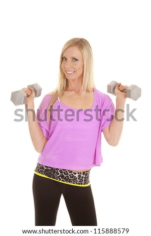 A woman with a smile on her face working out with her weights. - stock photo