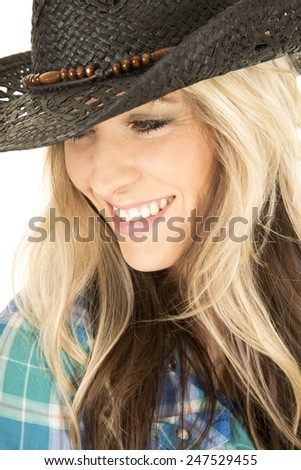 a woman with a smile wearing her western hat and blue plaid shirt. - stock photo