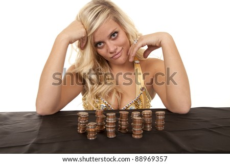A woman with a stack full of change in front of her with a small smile on her face. - stock photo