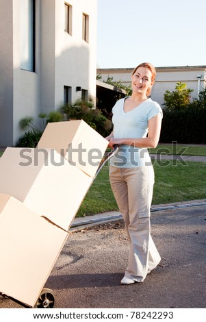 A woman with a stack of cardboard boxes on a trolly - stock photo